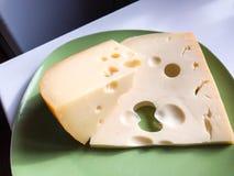 与孔的可口精华乳酪,说谎在一块绿色板材 两开胃大块 库存图片