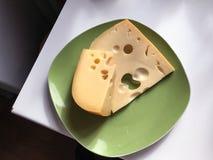 与孔的可口精华乳酪,说谎在一块绿色板材 两开胃大块 免版税库存照片