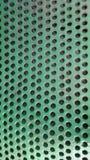 与孔的绿色纹理 与孔的垂直的背景 免版税库存照片