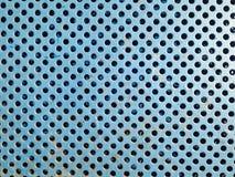 与孔的蓝色生锈的金属花格纹理关闭 库存照片