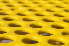 与孔纹理的黄色野餐桌 库存照片