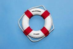 与字法'Bord'在德语在蓝纸背景翻译'在船上欢迎'的Willkommen的救生带 免版税图库摄影