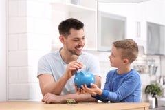 与存钱罐和金钱的家庭 免版税库存照片