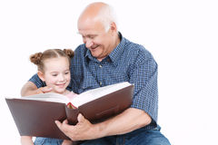 读与孙女的祖父一本书 免版税库存照片