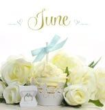 与季节性花和装饰的美丽的白色6月新娘题材杯形蛋糕6月 库存图片