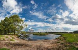 与孤独的渔夫、河和美丽的多云天空的壮观的全景春天夏天风景 免版税库存照片