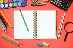 与学校和办公室文具,红色背景的空白的笔记薄 免版税库存照片