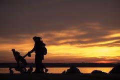 与孩子和一个婴孩的家庭摇篮车或婴儿推车剪影的 免版税库存照片