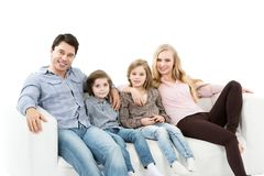 与孩子的一个愉快的家庭在被隔绝的长沙发 库存图片