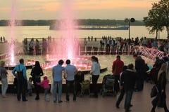 与孩子的人步行临近喷泉 免版税图库摄影