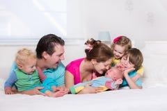 与孩子的大家庭在床上 免版税图库摄影