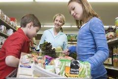与孩子的妇女购物在超级市场 库存图片