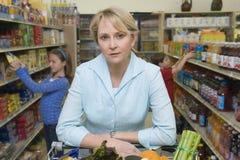 与孩子的妇女购物在超级市场 免版税库存图片