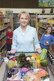 与孩子的妇女购物在超级市场 图库摄影