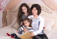 读与孩子的妈妈一本书 免版税库存照片