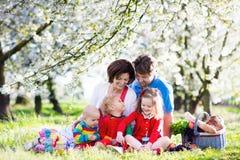 与孩子的家庭在野餐在春天庭院里 库存照片