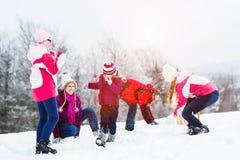 与孩子的家庭有雪球战斗在冬天 免版税库存照片