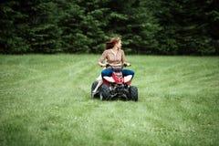 与孩子的家庭骑马在草 免版税库存图片