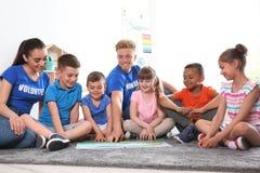 与孩子的年轻志愿者看书在地板上 免版税图库摄影