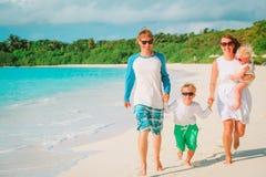 与孩子的愉快的家庭演奏在海滩的奔跑 库存照片