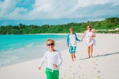 与孩子的愉快的家庭演奏在海滩的奔跑 图库摄影