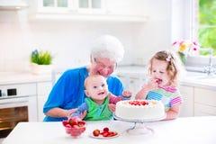 与孩子的愉快的祖母烘烤蛋糕 库存照片