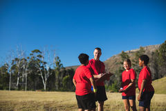 与孩子的教练员谈论在剪贴板在新兵训练所 免版税库存图片