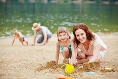 与孩子的父母戏剧在海滩 免版税库存图片