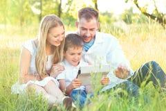 与孩子的年轻家庭使用片剂个人计算机在夏天公园 免版税图库摄影