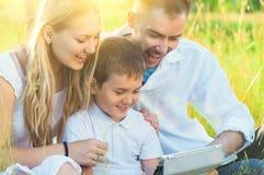 与孩子的年轻家庭使用片剂个人计算机在夏天公园 免版税库存照片