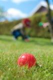 与孩子的Petanque红色球在背景中 库存照片