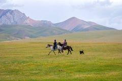 与孩子,吉尔吉斯斯坦配对骑马 库存照片