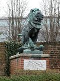 与它的爪子的持续在砖柱基的一头狮子的被雕刻的小组一只老鹰 免版税库存照片