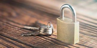 与安全,有钥匙的锁挂锁的标志的庄园概念在老木背景 库存图片