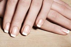 与完善的法式修剪的钉子 喜欢女性手 免版税图库摄影