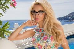 与完善面孔佩带的画象秀丽惊人的性感的白肤金发的模型太阳镜和典雅的白色比基尼泳装 图库摄影