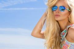 与完善面孔佩带的画象秀丽惊人的性感的白肤金发的模型太阳镜和典雅的白色比基尼泳装 免版税库存图片