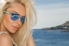 与完善面孔佩带的画象秀丽惊人的性感的白肤金发的模型太阳镜 免版税图库摄影