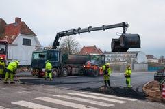 与完成一些柏油碎石地面工作的起重机的柏油碎石地面卸车 免版税库存照片