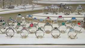 与宝石的各种各样的银色圆环和首饰由银制成在商店窗口 股票录像