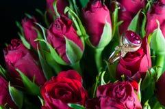 与宝石的真正的金戒指在红色玫瑰 免版税库存照片
