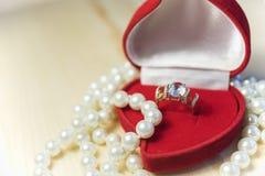 与宝石的金黄在一个红色礼物盒的圆环和珍珠 图库摄影