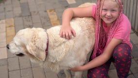与宠物的生活在一个现代城市-有抚摸她的在街道上的一次非常规的出现的一个女孩狗 股票视频
