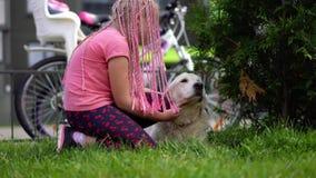 与宠物的生活在一个现代城市-有抚摸她的在街道上的一次非常规的出现的一个女孩狗 股票录像