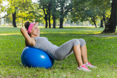 与室外普拉提的球的健身健康少妇锻炼 免版税图库摄影