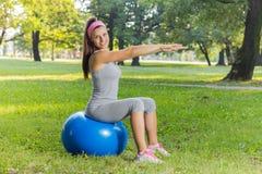与室外普拉提的球的健身健康少妇锻炼 免版税库存图片