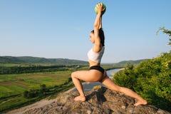 与室外的球的性感的深色的妇女健身辅导员训练 绿色森林山和蓝天背景 图库摄影