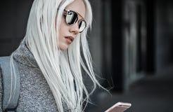 与室外的电话的白肤金发的模型 图库摄影