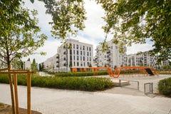 与室外设施和儿童的游乐场,新的公寓门面的现代居民住房  库存照片
