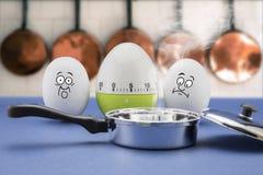 与害怕面孔看看的两个鸡蛋煎锅 免版税库存图片